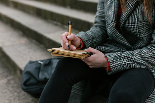 Woman writing in book while sitting on steps
