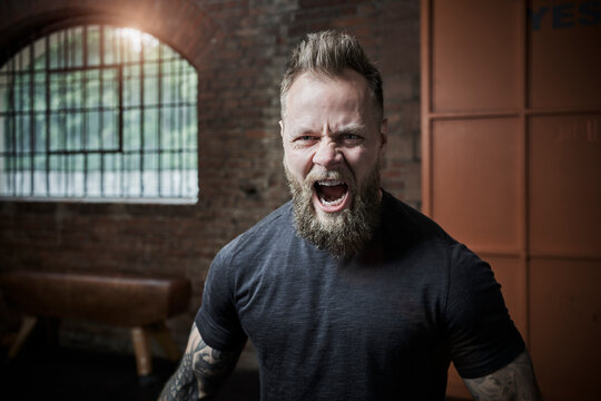 Bearded fitness instructor screaming in gym