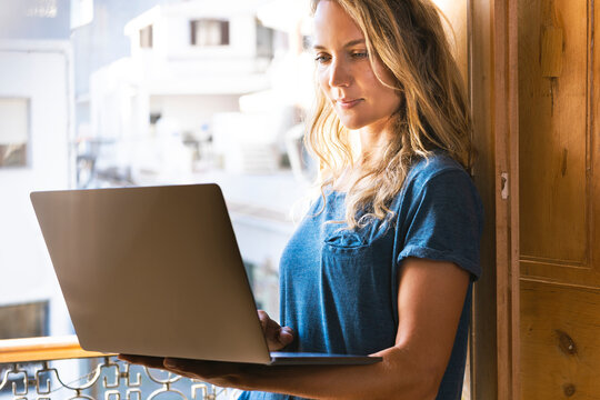 Woman concentrating while using laptop at home