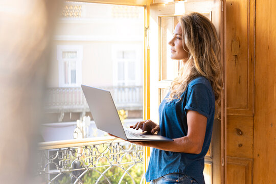 Thoughtful woman with laptop looking through window at home