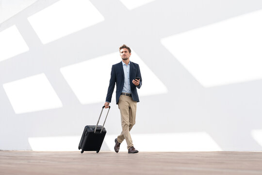 Mid adult businessman with mobile phone and wheeled luggage walking against white wall