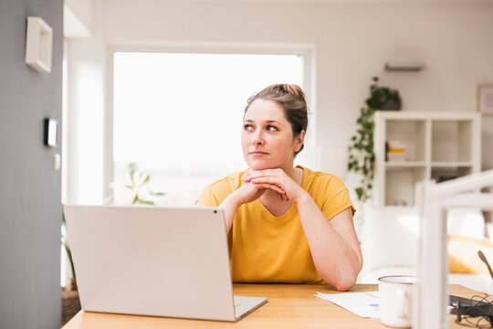 Contemplated female entrepreneur sitting with laptop at desk looking away
