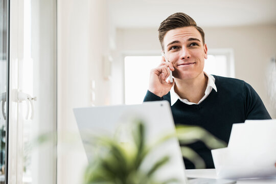 Smiling businessman talking on smart phone while sitting in home office