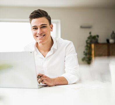Smiling male professional using laptop while sitting at table in home office