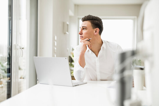 Young male professional looking through window while sitting in home office