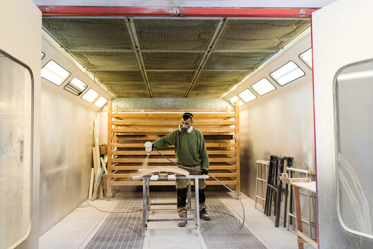 Male carpenter with protective face mask spraying paint on wood material in spraybooth
