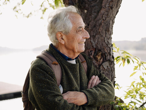 Smiling man with backpack looking away while leaning on tree