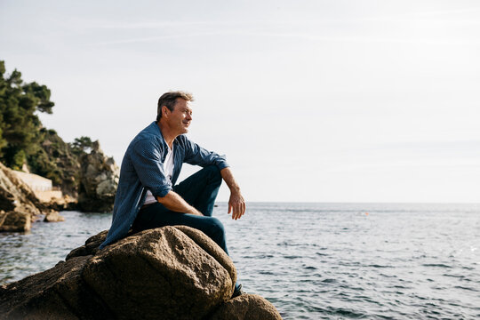 Thoughtful mature man sitting on rock against clear sky