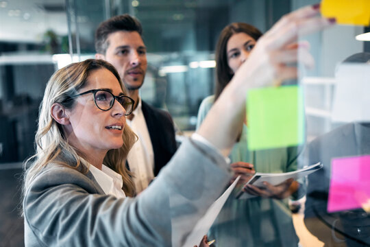 Businesswoman reading adhesive note on glass wall while standing with colleague at office