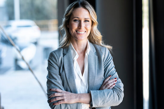 Confident businesswoman smiling while standing at office