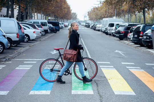 Woman with bicycle walking on zebra crossing while looking away