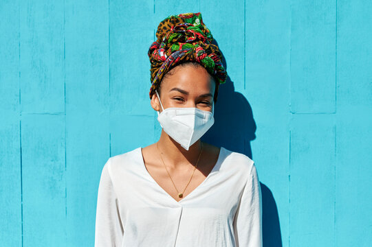 Woman wearing protective face mask and headscarf staring while standing against blue wall