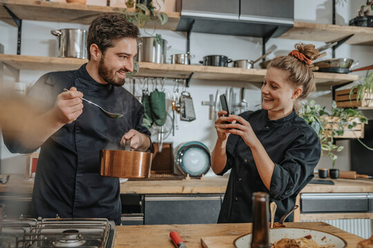 Young chef taking photo of colleague tasting soup while standing in kitchen