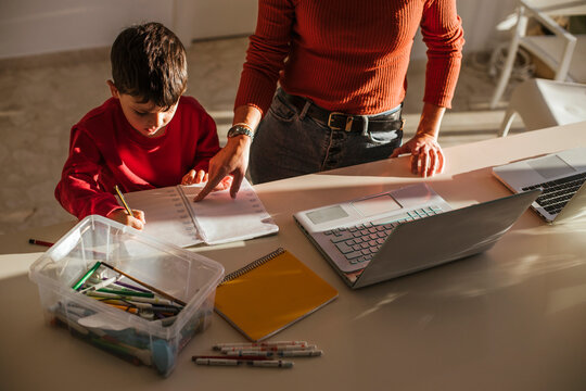 Mother assisting son in studies at dining table at home