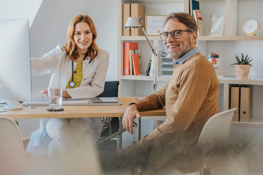 Female doctor and patient smiling while sitting at doctor's office