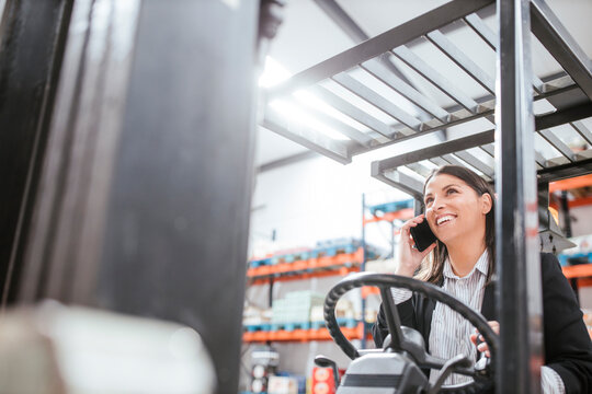 Cheerful female manager talking on mobile phone while operating forklift at warehouse