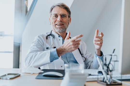 Smiling male doctor gesturing while sitting at doctor's office