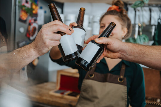 Chefs toasting beer bottles while standing in kitchen