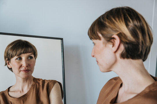 Thoughtful woman looking at reflection in mirror