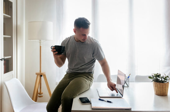 Businessman holding coffee cup using laptop while sitting on desk at home office