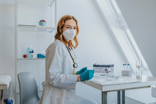 Female doctor wearing protective face mask siting by desk at examination room