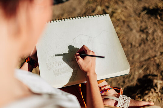 Young woman artist drawing in spiral notebook