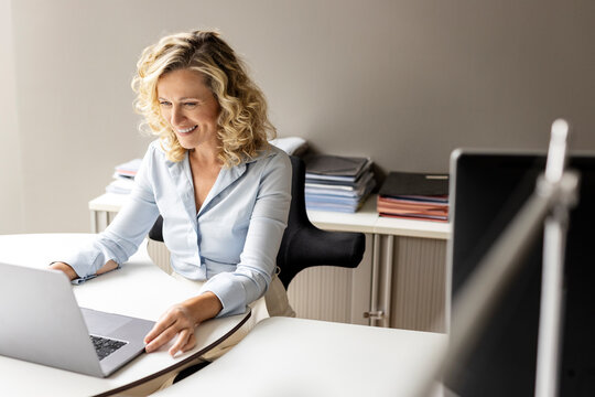 Smiling businesswoman with laptop sitting at desk in office