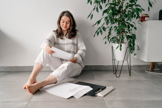 Female entrepreneur reading documents while sitting against wall at home