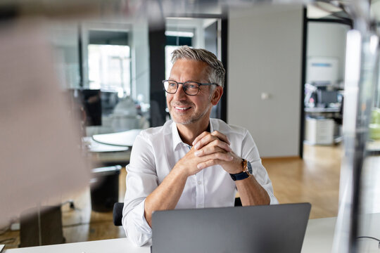 Smiling businessman with hands clasped looking away while sitting at desk in office