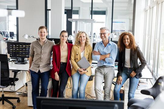 Smiling male and female entrepreneurs leaning on desk in office