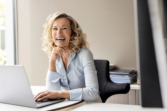 Laughing female business professional with laptop sitting in office