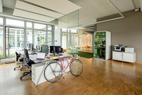 Bicycle, laptop and computers at desk in open plan office