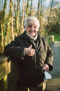 Smiling senior woman showing thumbs up while standing on footbridge during COVID-19