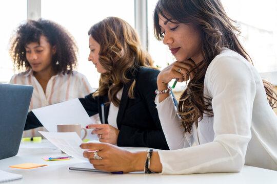 Beautiful female entrepreneurs discussing in office