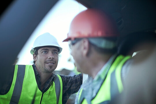 Two male construction workers chattingÔøΩby car