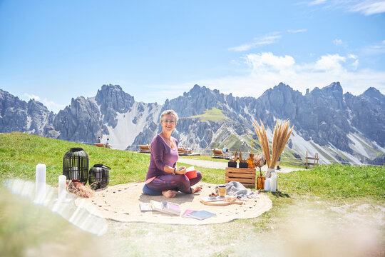 Smiling woman with book sitting on carpet against mountain