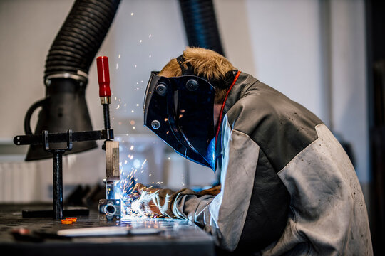 Welder with coveralls working at factory