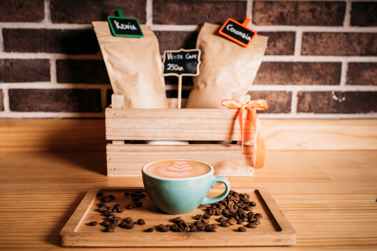 Coffee with latte art amidst coffee beans on wooden tray