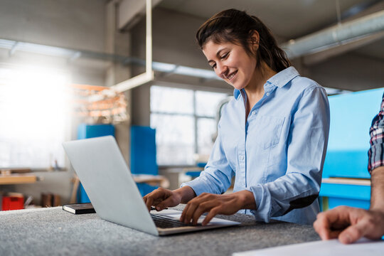 Smiling businesswoman working on laptop while standing by colleague at industry