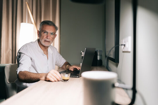 Mature man holding coffee cup while sitting at desk with laptop in hotel room