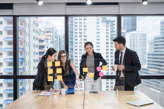 Group of multiethnic business colleagues analyzing and discussing about business plan with sticky note on board in the office