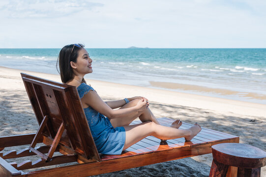 Beautiful young asian woman relaxing and sunbathing on wooden lounge on the beach in tropical sea