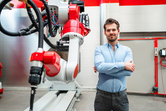 Male engineer with arms crossed standing at robotics in factory
