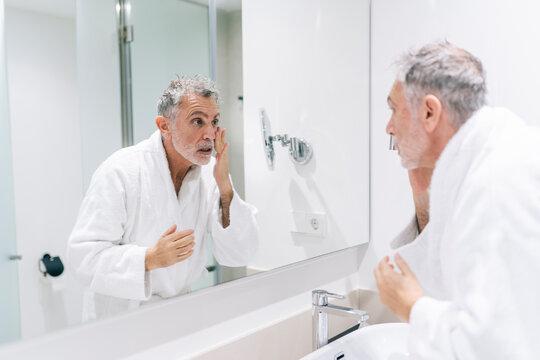 Surprised man wearing bathrobe looking at mirror in hotel bathroom