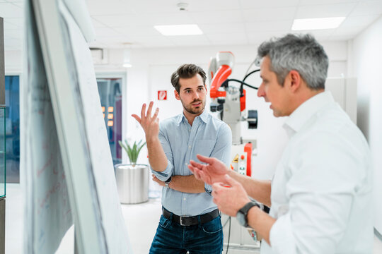 Male engineers gesturing while discussing business plans at white board in factory