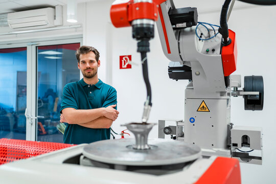 Smiling young man with arms crossed standing at automatic machinery in factory