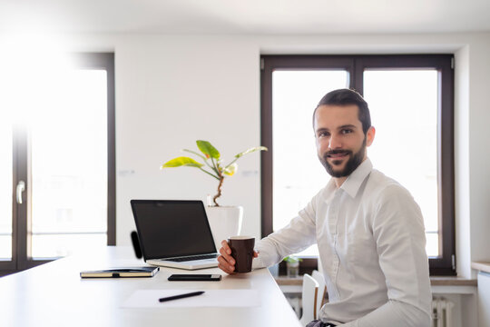 Smiling young businessman with coffee cup sitting by laptop at office