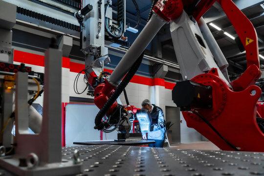 Mature worker with welding helmet working at robotics in factory