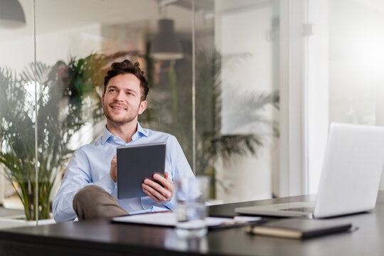 Businessman with digital tablet looking away at office