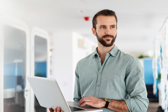 Young male professional with laptop standing at office